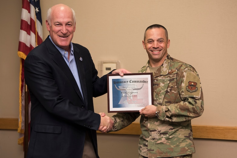 Sid Cauthorn, 47th Flying Training Wing honorary wing commander, receives an award from Col. Lee Gentile, 47th FTW commander, in Del Rio, Texas, Oct. 15, 2019. The honorary wing commander program enables the base and local community to develop and encourage the sharing of ideas, experiences and friendships. (U.S. Air Force photo by Senior Airman Marco A. Gomez)