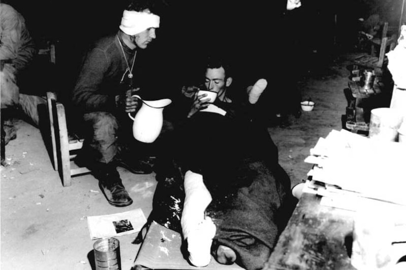 A wounded soldier, whose leg is bandaged, raises his head to sip from a large bowl while lying on the floor under a blanket. Another soldier, whose head is bandaged, sits beside him in a chair holding a pitcher and prepares to pour refill the bowl held by his wounded comrade.