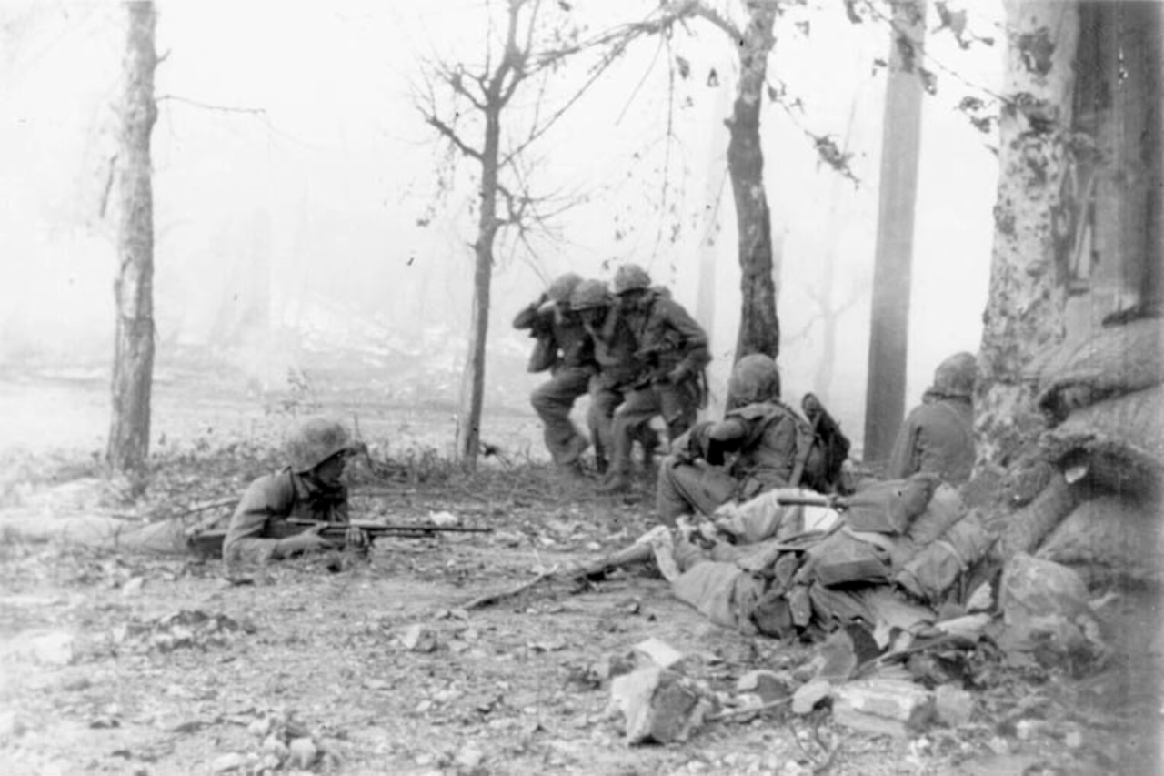 Two soldiers carry a third between them past sparse trees on a battlefield. In the foreground, three other soldiers holding weapons keep watch.