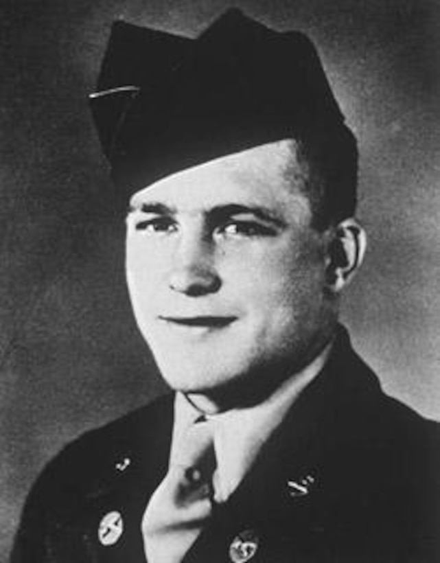 A soldier in his dress uniform smiles for an official photo.