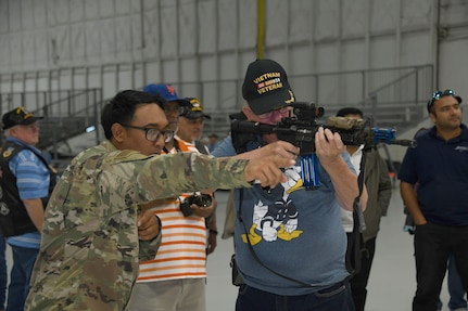 Staff Sgt. Colin Jamero, left, 11th Security Support Squadron, helps a Vietnam Security Police Association member with a simulated firing range during the association's 25th anniversary held at Joint Base Andrews, Md., Oct. 10, 2019. During the day, the veterans were also shown a military working dog demonstration, and a weapons and equipment display, all while getting to spend some time with JBA defenders. (U.S. Air Force photo by Airman 1st Class Spencer Slocum)
