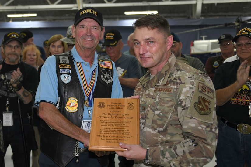 Jerry Nelson, Vietnam Security Police Association president, left, presents Col. Joseph A. Engelbrecht III, 11th Security Forces Group commander, a plaque of appreciation for hosting the assocaition's 25th anniversary at Joint Base Andrews, Md., Oct. 10, 2019. The VSPA presented awards and challenge coins to multiple Airmen for supporting the VSPA event. (U.S. Air Force photo by Airman 1st Class Spencer Slocum)