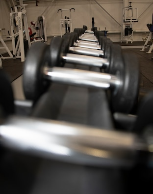 Dumbells sit on a rack in the Nose Dock Gym Oct. 11. 2019 at Travis Air Force Base, California. The new gym at Building 844 was facilitated through existing base funds, equipment donations and volunteer work by the 60th Mission Support Group. (U.S. Air Force photo by Heide Couch)