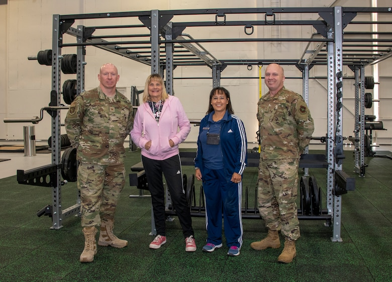 From left to right, U.S. Air Force Col. Victor Beeler, 60th Mission Support Group, commander, Barbara Green, programs director, and Tanya McCormick, fitness and sports director, both with the 60th Force Support Squadron and Chief Master Sgt. Matthew Pulsipher, 60th MSG interim superintendent, stand inside the Nose Dock Gym Oct. 11, 2019, at Travis Air Force Base, California. The new gym at Building 844 was facilitated through existing base funds, equipment donations and volunteer work by the 60th Mission Support Group. (U.S. Air Force photo by Heide Couch)