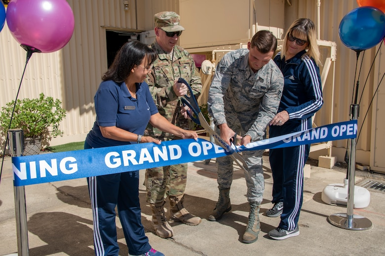 From left to right, Tanya McCormick, 60th Force Support Squadron fitness and sports center manager, U.S. Air Force Col. Victor Beeler, 60th Mission Support Group commander, Senior Airman Joshua Knutson, fitness specialist and Barbara Green, programs director both with the 60th FSS, cut the ribbon to open the Nose Dock Gym Oct. 15, at Travis Air Force Base, California. The new gym at Building 844 was facilitated through existing base funds, equipment donations and volunteer work by the 60th Mission Support Group. The new facility is located on Nose Dock Lane off Ragsdale and V Street. Current operating hours are 6 – 8 and 4–8 p.m., subject to change. (U.S. Air Force photo by Heide Couch)