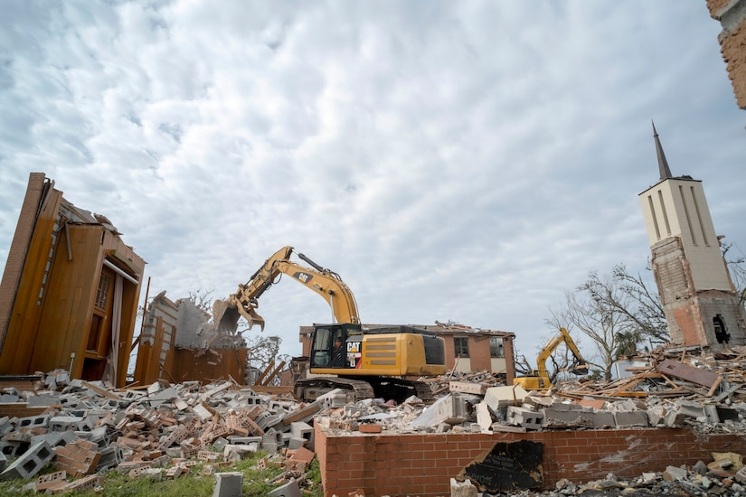 Industrial equipment tears down a building.