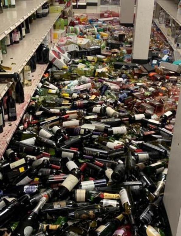Hundreds of glass wine bottles are on the floor of a retail facility.