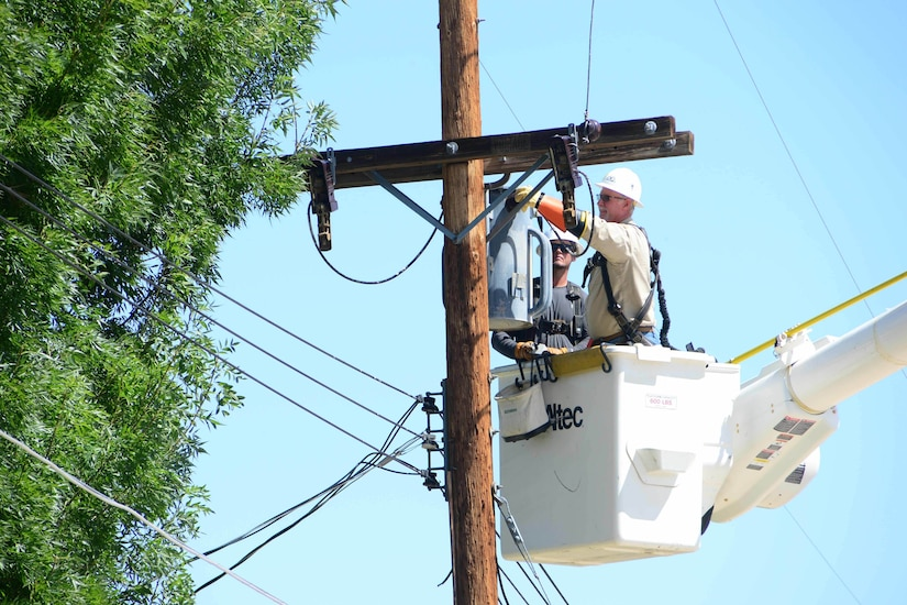 Men in a bucket crane work on a power transformer that sits atop a wooden pole.