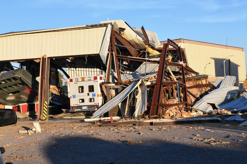 A facility housing an ambulance has crumbled down around a vehicle.