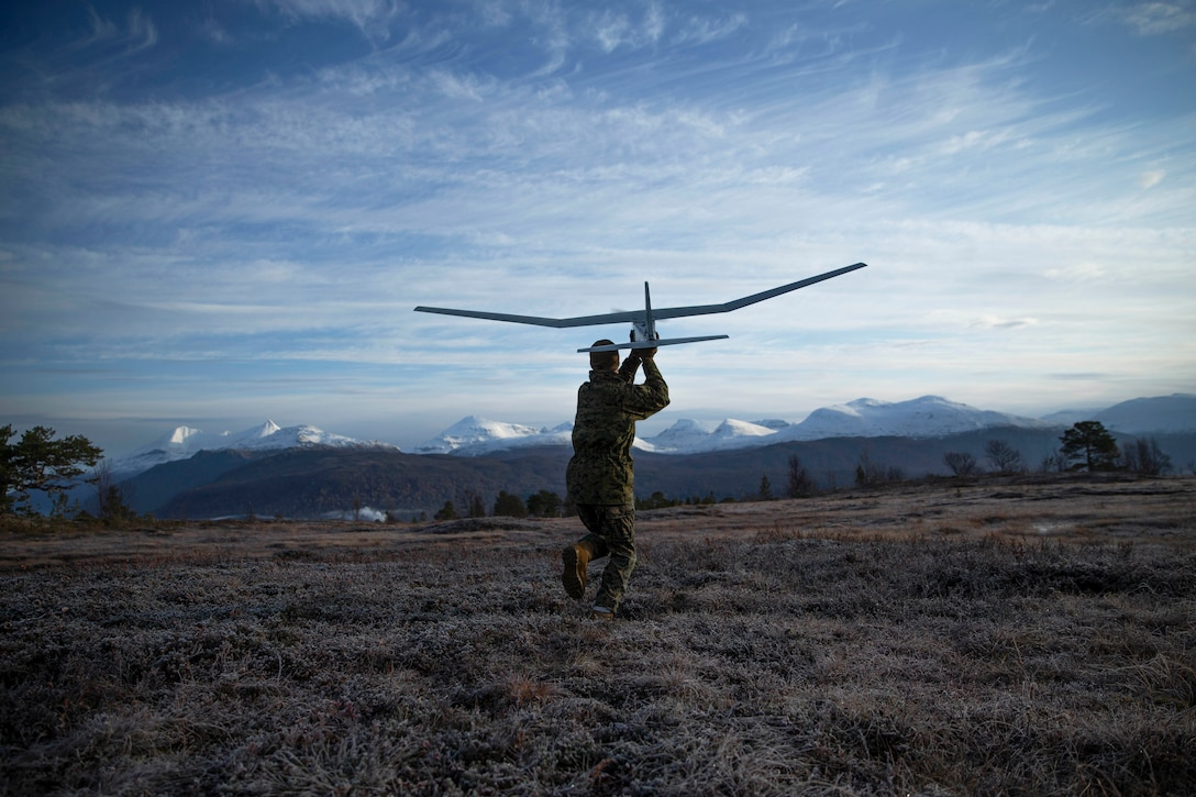 A Marine throws a small unmanned aerial system with mountains in the background.