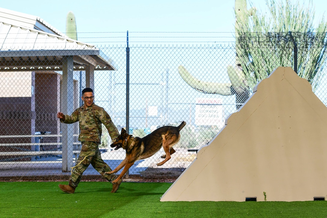 An airman runs alongside a dog.