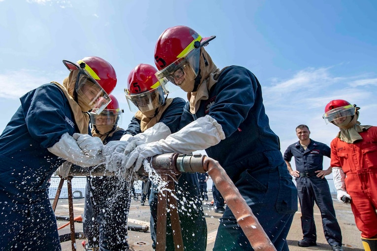 A group of sailors use their hands to stop water for pouring out of a hole in a water hose.