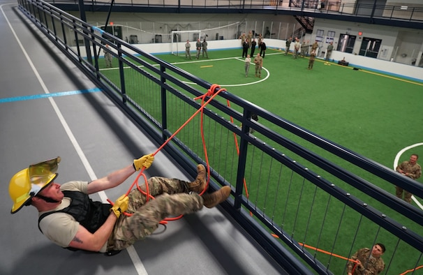 Maj. TJ Gabrielson, 319th Civil Engineer Squadron operations flight commander, pulls a weighted bag up to the second floor of the fieldhouse during the base commander's annual firefighter challenge Oct. 10, 2019, as part of National Fire Prevention Week on Grand Forks Air Force Base, North Dakota. Gabrielson's team competed against four others in a series of six firefighting-themed strength challenges, and took home the trophy with a winning time of less than two minutes. (U.S. Air Force photo by Senior Airman Elora J. Martinez)