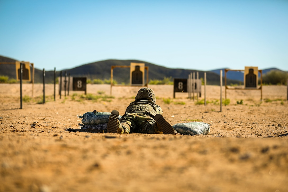 A soldier lies on the ground shooting at targets.