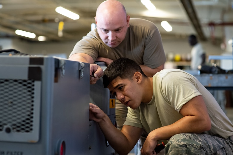 Tech. Sgt. Boris Raykhel, left, and Airman 1st Class Javier Saldana, 388th Aerospace Ground Equipment Flight, work on a munitions loader during maintenance at Hill Air Force Base, Utah, Oct. 4, 2019. Unit Airmen maintain over 600 pieces of equipment that support the mission of crew chiefs, avionics, weapons and ammo troops. (U.S. Air Force photo by R. Nial Bradshaw)