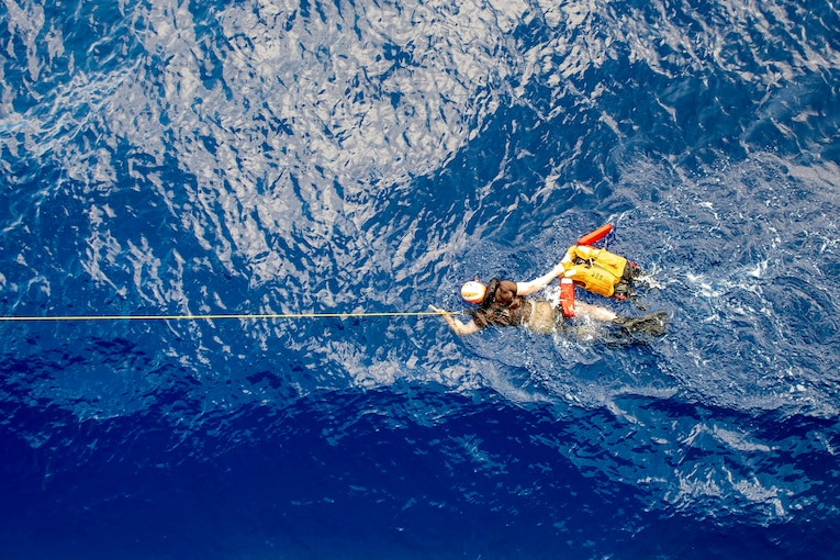 A sailor swims in bright blue water, holding a line and an inflated life vest.