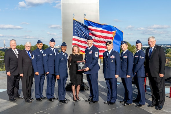 Col. Gavin Marks, 55th Wing commander, Chief Master Sgt. Brian Thomas, 55th Wing command chief, and five other wing members accept the award from Jonna Doolittle, granddaughter of James Doolittle, at the Air Force Memorial in Arlington, Virginia Oct. 9, 2019.
