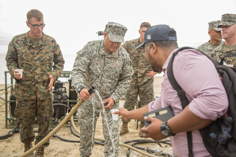 Colombian military officer fills a cup with water from a hose. A civilian is holding the cup, and Marines in uniform observe.