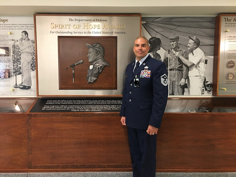 "U.S. Air Force Master Sgt. Jorge L. Arce, 86th Aircraft Maintenance Squadron first sergeant, poses for a photo in front of the Bob Hope ""Spirit of Hope"" award wall at the Pentagon, Sept. 27, 2019. (Courtesy photo/Photo edited to black out security badges)"