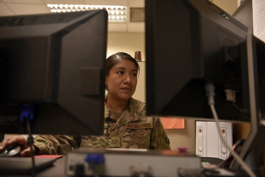 Tech. Sgt. Alejandra Martinez, 379th Air Expeditionary Wing security manager and executive administration non-commissioned officer-in-charge, reviews policies and procedures at her workstation at Al Udeid Air Base, Qatar on Oct. 18, 2019.