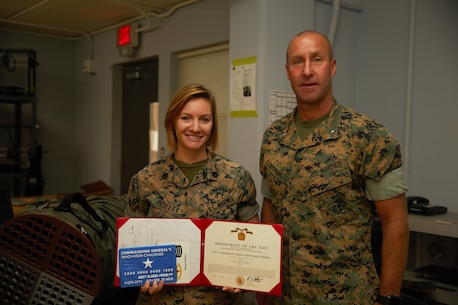 U.S. Marine Staff Sgt. Elissa Pedelty receives $1,000 and a Navy and Marine Corps Achievement Medal for her winning idea in designing an Environmental Control Unit (ECU) duct cover at MakerSpace, Camp Lejeune, North Carolina, on Oct. 16, 2019. MakerSpace facilitates the 2nd Marine Logistics Group Commanding General's Innovation Challenge, where Marines and Sailors submit innovative ideas to design an interesting culture that explores new ideas to improve policies, procedures or products.  (U.S. Marine Corps photo by Sgt. Ashley Lawson)