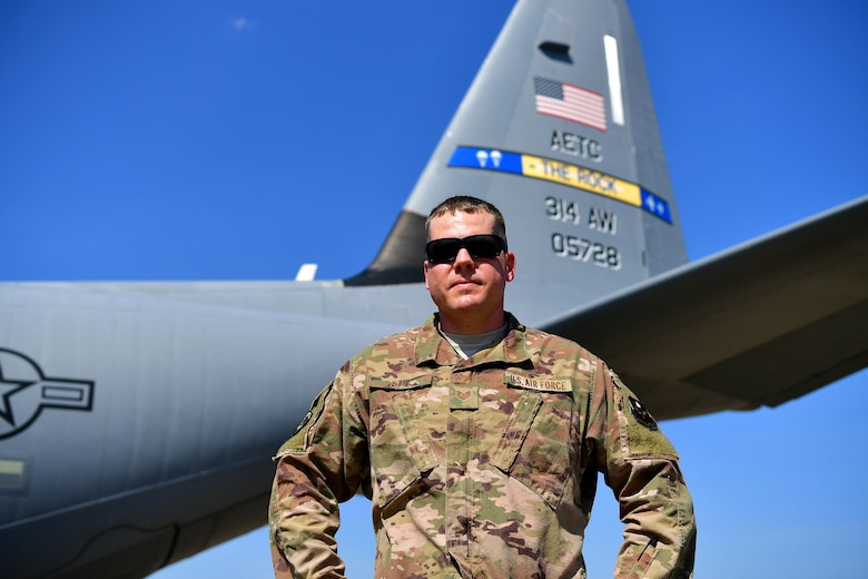 A man in the OCP uniform stands in front of a C-130J.