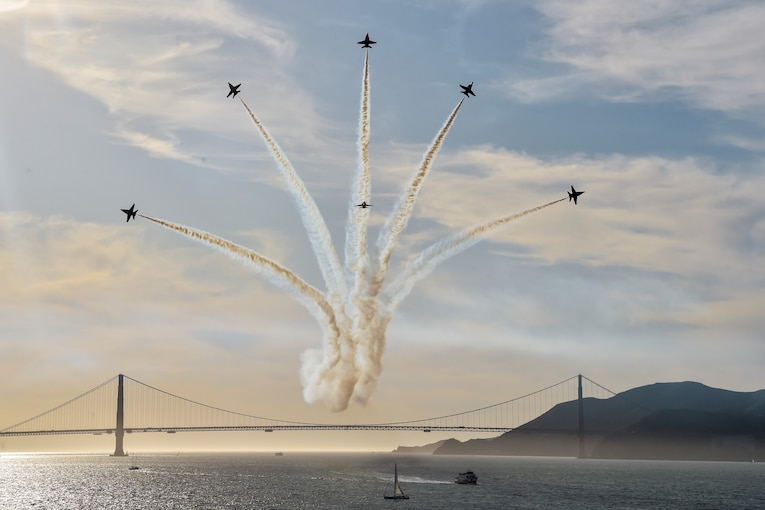 Six jets fly fan out in a formation over the Golden Gate bridge.