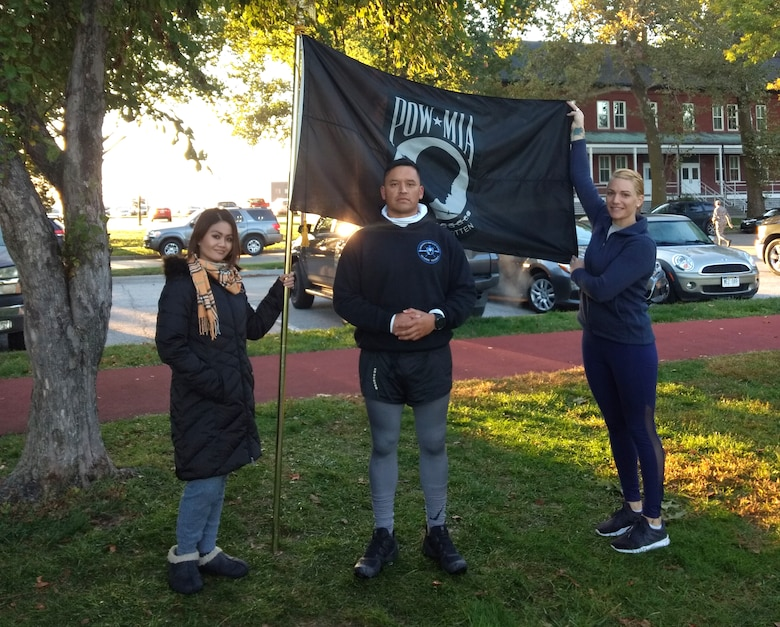 runners pose with POW/MIA flag after running 24 hours