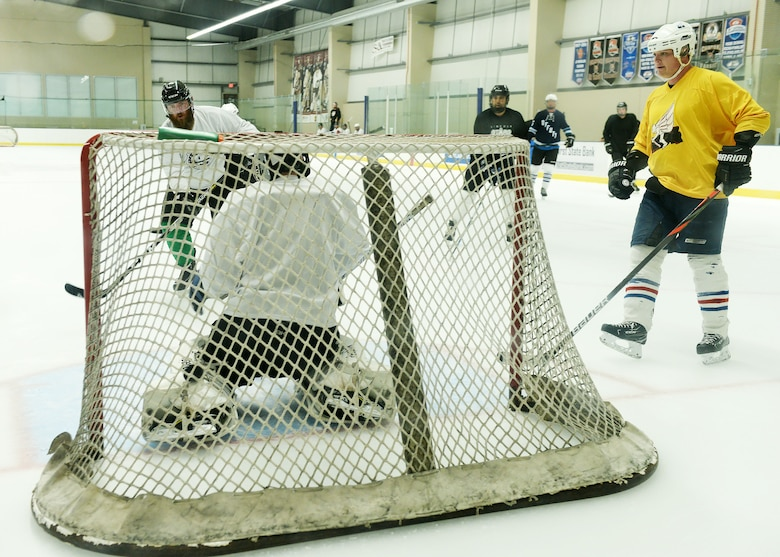 The Nebraska Warriors hockey team scrimmages at Ralston Arena in Ralston, Nebraska. Several players approach the net as a goalie tries to defend.