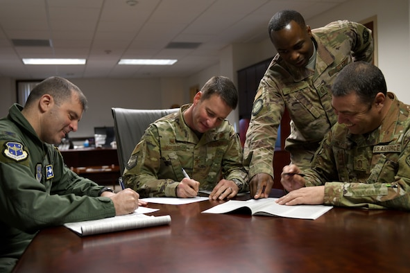 Men in military uniforms sign a piece of paper.