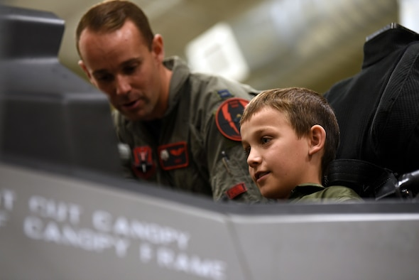 Brody, with Make-A-Wish Utah, listens as Capt. Buck Horn, an F-35A Lightning II pilot shows him around the cockpit of an F-35A egress trainer. A group of children visited the 388th Fighter Wing at Hill Air Force Base, Utah, where they spent the day learning what it's like to be a pilot. They received flight suits, name tapes, patches, and wings. (U.S. Air Force photo by Micah Garbarino)
