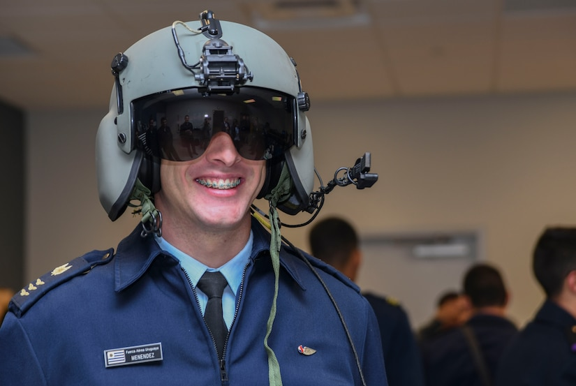 A cadet from the Latin American Cadet Initiative poses for a photo after trying on a HGU-56/P helmet during a 1st Helicopter Squadron tour on Joint Base Andrews, Md., Oct. 16, 2019.