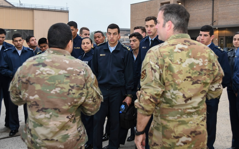 Master Sgt. Jose Velazquez, left, 811th Operations Support Squadrons flight chief, and Tech. Sgt. David Prato, right, 1st Helicopter Squadron UH-1N special missions aviator instructor, explain the capabilities of a UH-1N Iroquois to cadets from the Latin American Cadet Initiative during a 1st Helicopter Squadron tour on Joint Base Andrews, Md., Oct. 16, 2019.