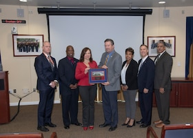 Five men and two women pose with a plaque after the HQC Hispanic Heritage Month observance.