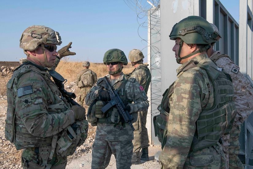 Soldiers in camouflage uniforms and protective gear talk near a wall.
