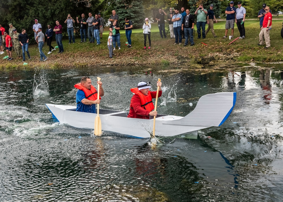 Two men paddle a canoe made of cardboard