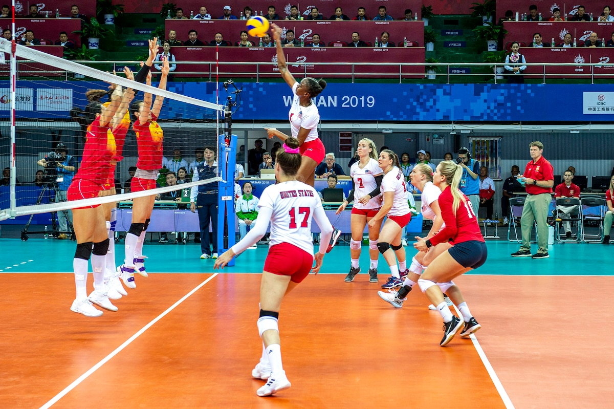 A U.S. athlete leaps and hits a ball as her teammates look on and opponents raise their arms on the other side of the net.