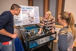 Corinne Beach, a STEM coordinator with Puget Sound Naval Shipyard & Intermediate Maintenance Facility uses a model to demonstrate a dry-dock pump for educators from South Kitsap High School in Port Orchard, Wash.