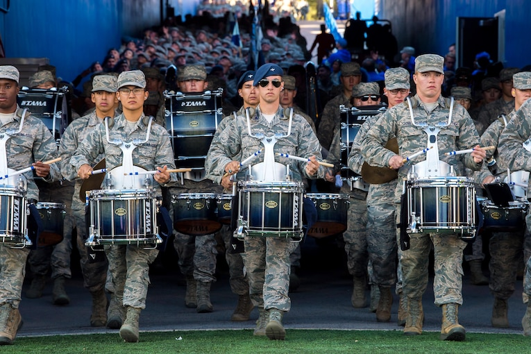 A large band marches through a tunnel.