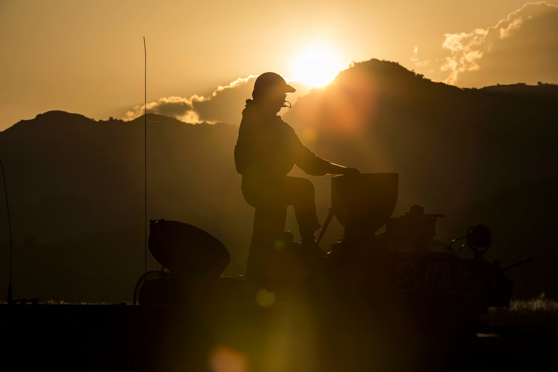 The silhouette of a Marine standing on a equipment with mountains in the background.