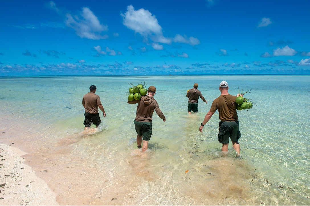 Four sailors wade through clear water carrying green coconuts.