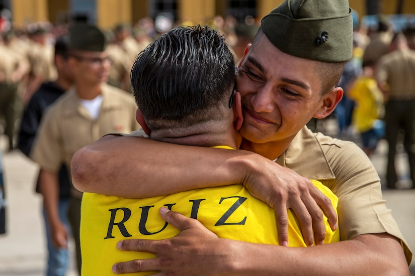 A Marine closes his eyes and smiles while hugging a civilian.