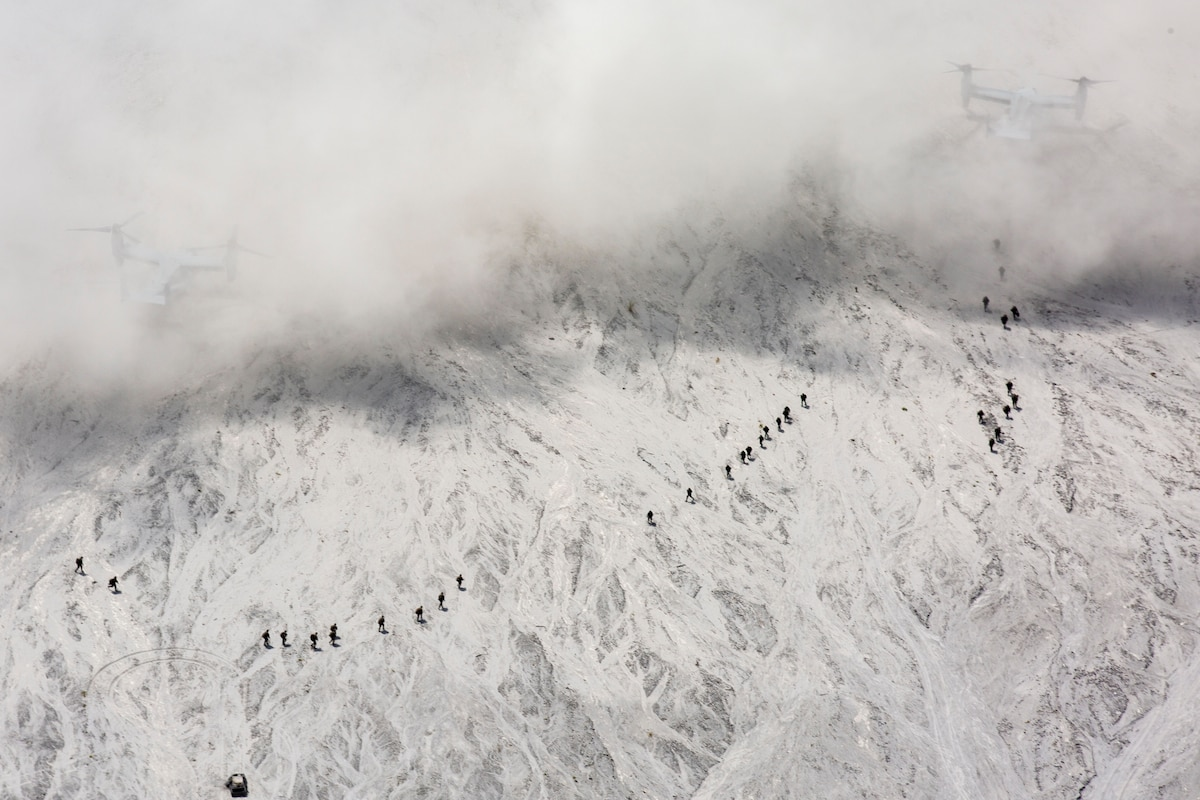 A group of service members climb a mountain.