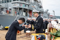 Commanding officer of Avenger-class mine countermeasures ship USS Pioneer (MCM 9), Lt. Cmdr. Bobby Wayland, gives a command ball cap to the mayor of Uki city, Kenshi Morita.