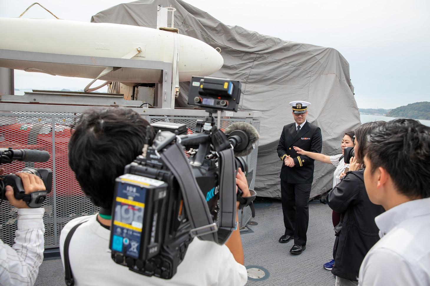 Lt. j.g. Scott Sansing, main propulsion officer of Avenger-class mine countermeasures ship USS Pioneer (MCM 9) gives a ship tour to Uki city media.