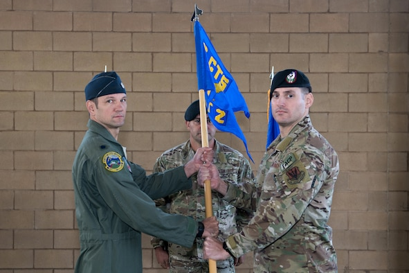 U.S. Air Force Lt. Col. James Kappes (left), 6th Combat Training Squadron operations officer, Camp Bullis, presents the Detachment 2, Combat Training Squadron guidon to Capt. Daniel Hill (right), incoming commander, during the activation ceremony Sept. 17, 2019, at Joint Base San Antonio-Medina Annex, Texas.