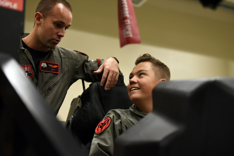 Ethan, with Make-A-Wish Utah is briefed by Capt. Buck Horn in an F-35A Lightning II egress trainer at Hill Air Force Base, Utah. A group of children visited the 388th Fighter Wing where they spent the day learning what it's like to be a pilot. They received flight suits, name tapes, patches, and wings. (U.S. Air Force photo by Micah Garbarino)