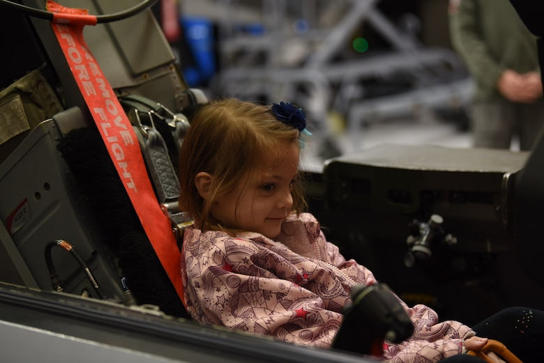 Sarah, with Make-A-Wish Utah, sits in the cockpit of an F-16 trainer at the 388th Fighter Wing. A group of children visited the 388th Fighter Wing where they spent the day learning what it's like to be a pilot. They received flight suits, name tapes, patches, and wings. (U.S. Air Force photo by Micah Garbarino)
