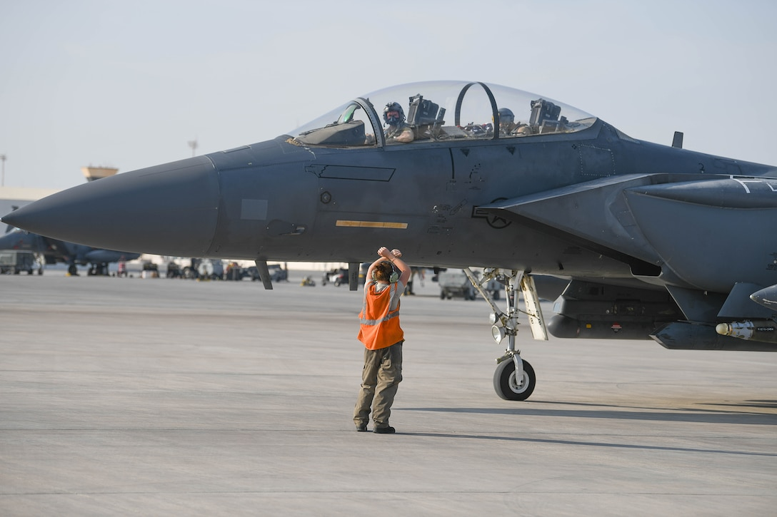 A crew chief from the 380th Expeditionary Aircraft Maintenance Squadron marshals a U.S. Air Force F-15E Strike Eagle to park Oct. 18, 2019, at Al Dhafra Air Base,