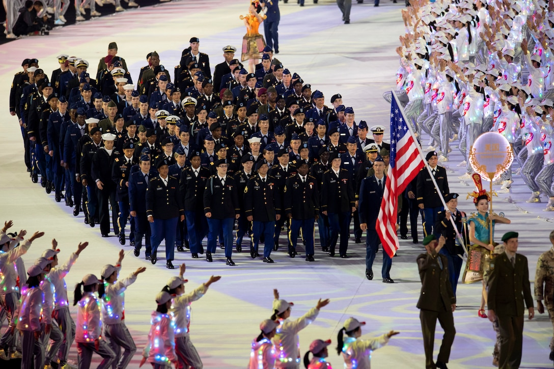 A large group of military athletes march in a parade.